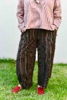 מכנסיים מדגם ג׳וזף מבד קורדרוי עם פסים בצבעים של חום-ירוק בקבוק-בז׳ על רקע שחור
