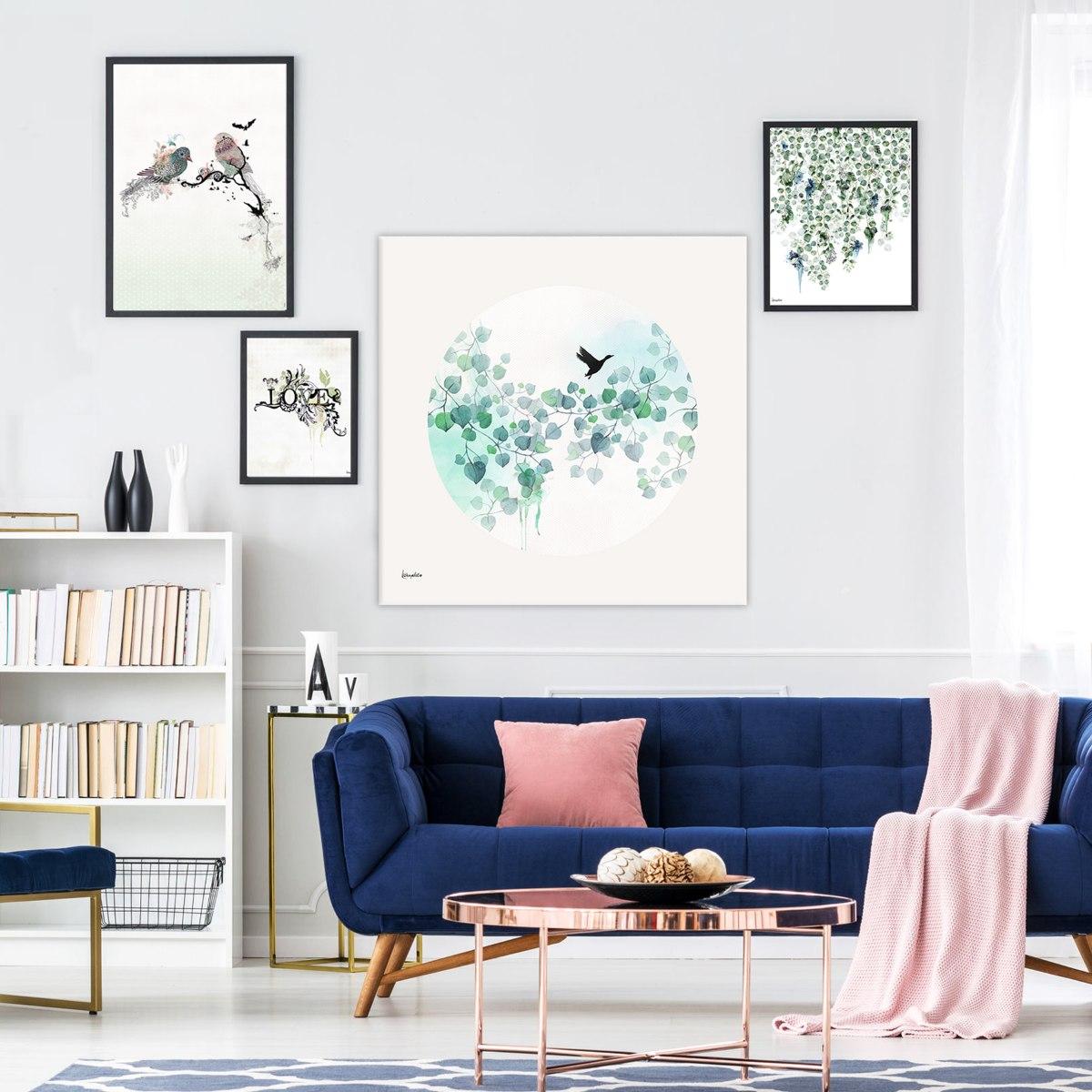 קיר גלריה של הדפסים שונים מעל ספה כחולה