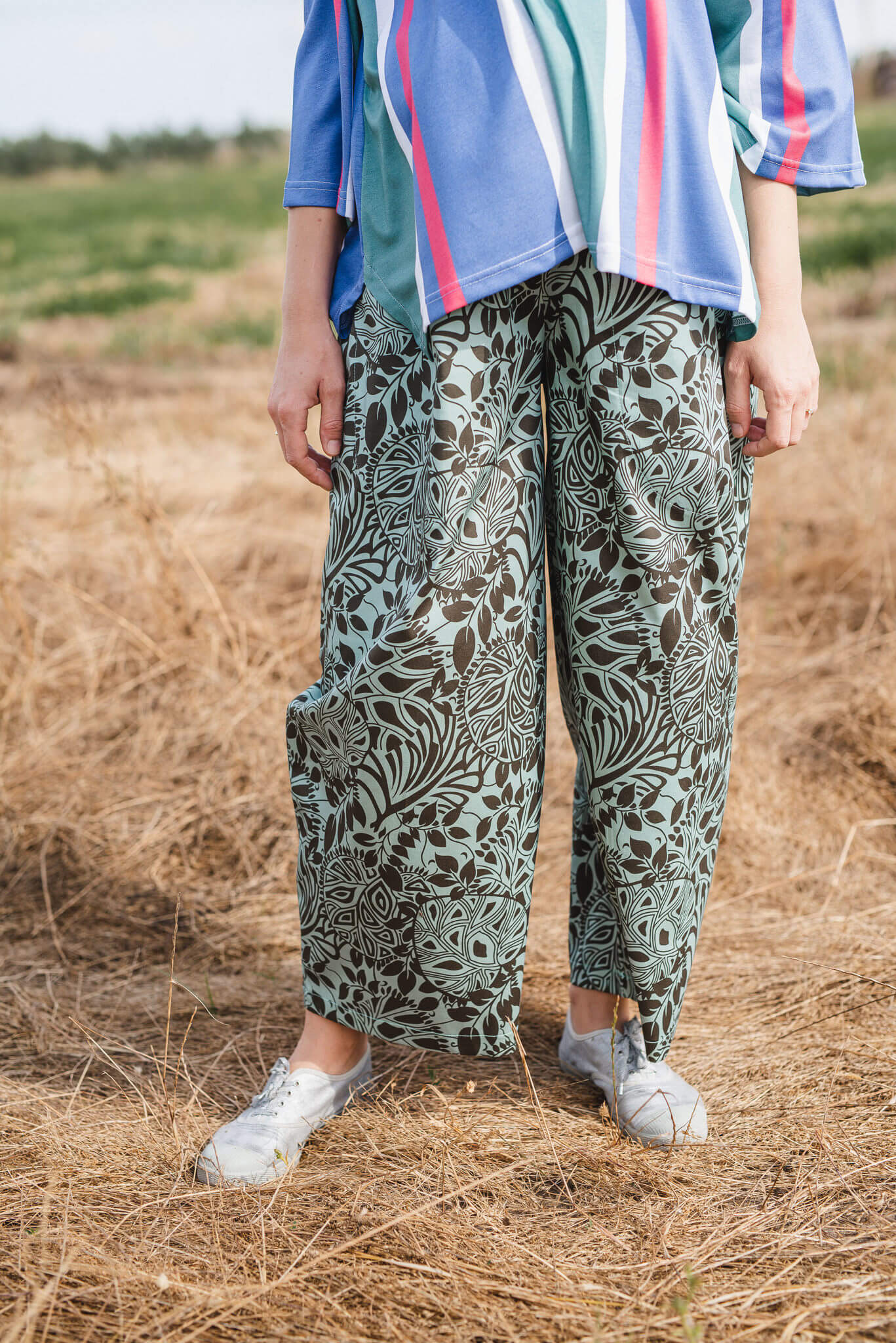 מכנסיים מדגם מיכאלה עם הדפס עלים על רקע ירקרק