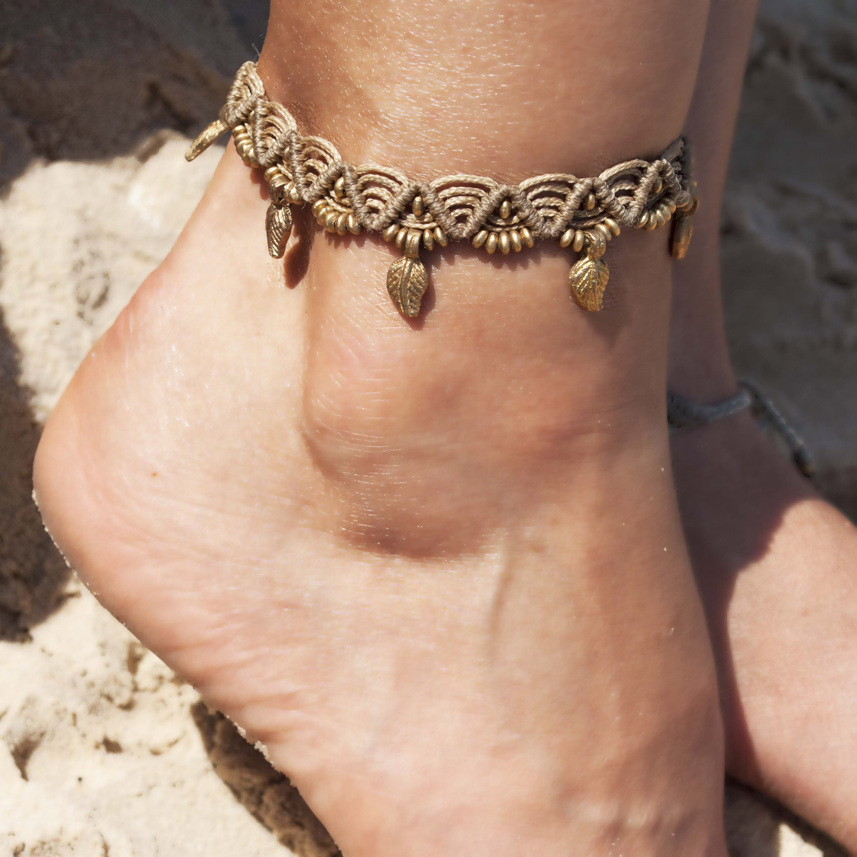 צמיד רגל מקרמה בז' עם חרוזי בראס ותליוני עלים