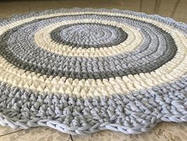שטיח סרוג בגוונים רכים של תכלת, אפור, שמנת