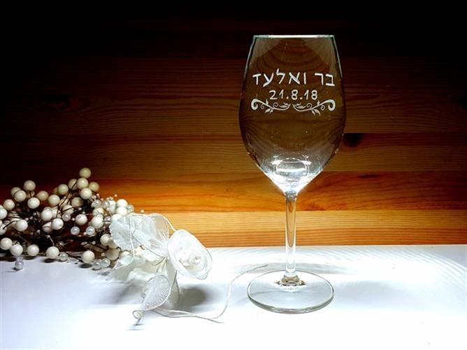 כוס חופה עם עיטור עלים מתחת לשמות בני הזוג ותאריך לועזי