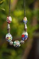 שרשרת עור עם חרוזים עתיקים מתקופות שונות מכסף וזכוכית. חרוזים מצויירים צבעוניים ועתיקים
