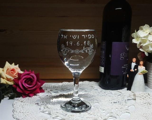 כוס חופה עם עיטור פרחים מתחת לשמות בני הזוג ותאריך לועזי
