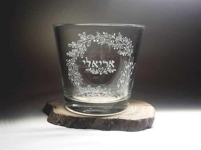 עציץ זכוכית עגול עם שם אחד ועיטורים סביבו